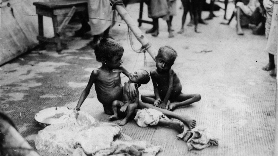 Two young children sat on the floor naked and emaciated from starvation. One is cradling a small baby.
