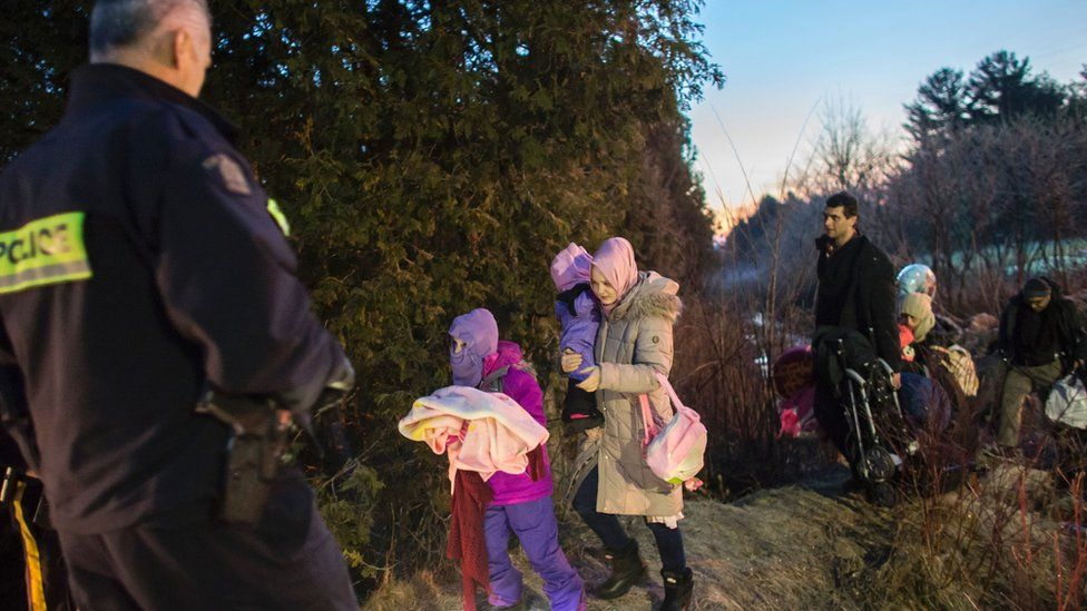 RCMP officers look on as an extended family of seven people from Turkey illegally cross the US-Canada border just before dawn on February 28, 2017 near Hemmingford, Quebec.
