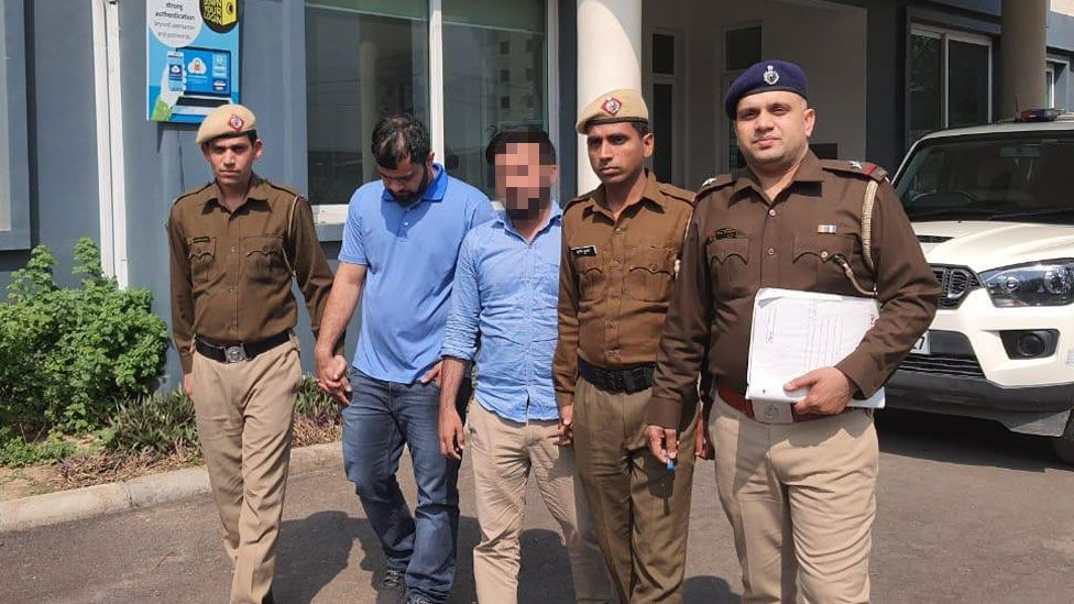 Two men in blue shirts are flanked by Indian police officers outside a building