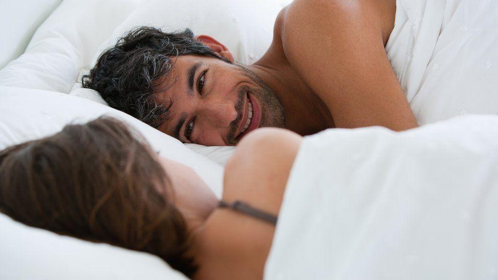 Man in bed looking happy