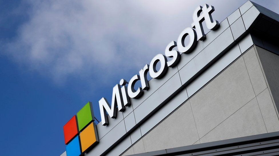 The Microsoft logo on a building in front a bright blue sky