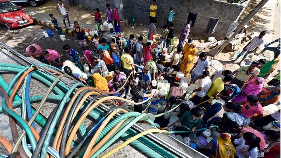 Residents filling empty containers with drinking water from a municipal tanker, at Vivekanand Camp, in Chanakyapuri on April 17 in Delhi