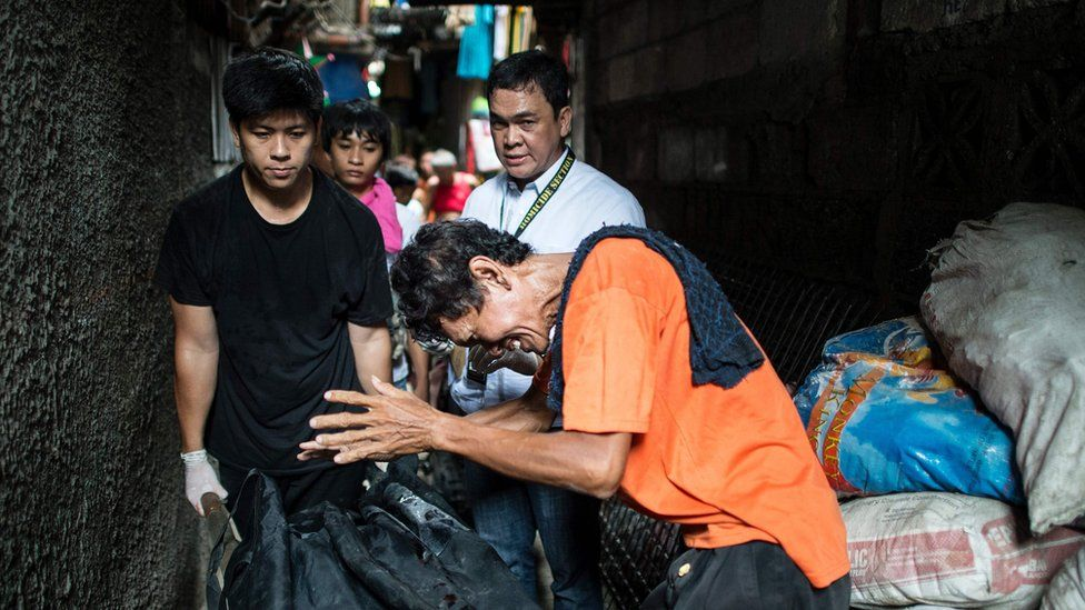 This picture taken on 1 September 2016, shows the grieving father of a suspected drug user killed by the police in Manila, as another man wheels the body away in a bag.
