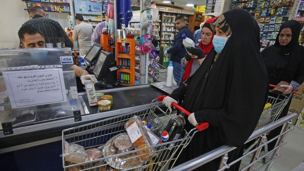 A woman waits at the till of a supermarket in Baghdad before the start of a curfew
