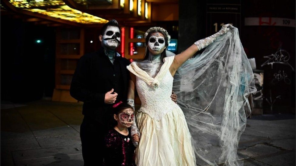 A couple and their daughter show off their costumes during the Catrinas parade.