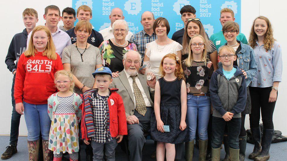Dan Puw, enillydd Medal Syr T H Parry Williams, yn dathlu'r achlysur gyda'i blant a'i wyrion. // Dan Puw, winner of the T H Parry Williams Medal, celebrates with his family.