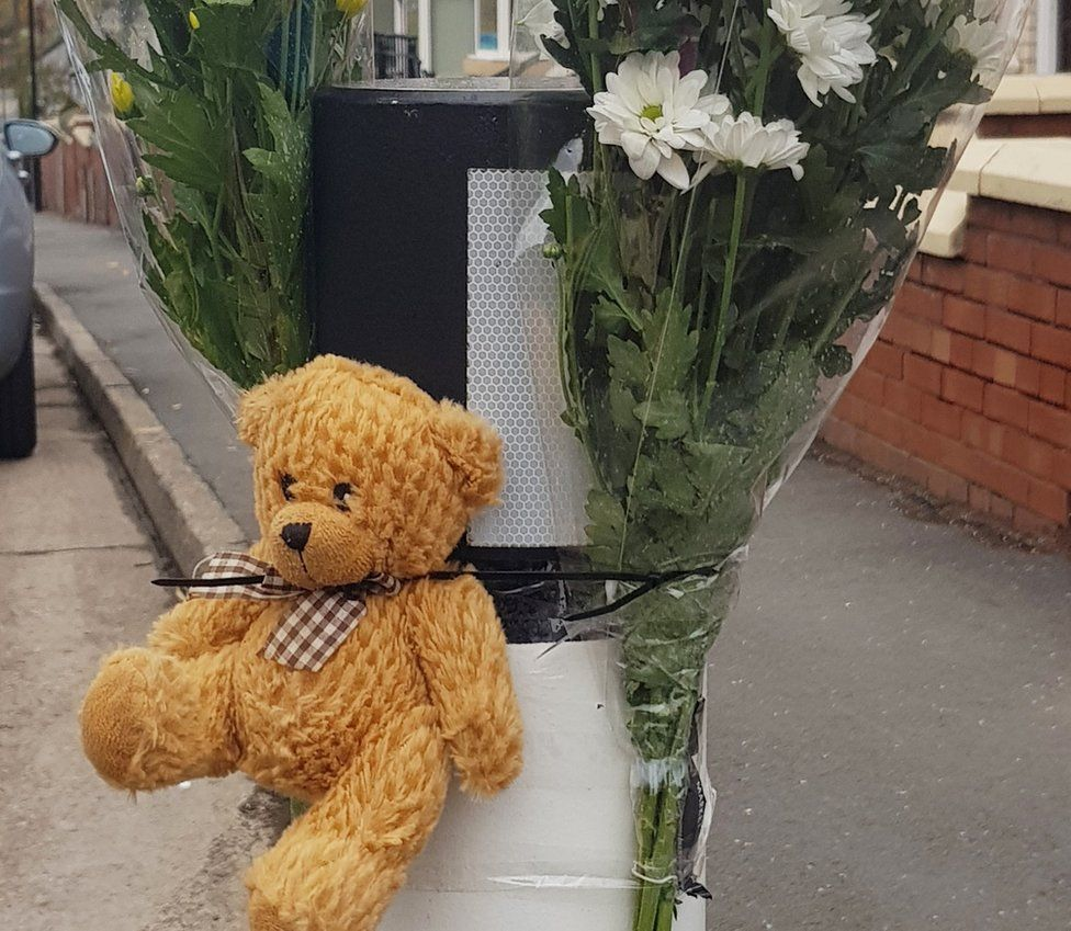 Floral tribute and teddy bear