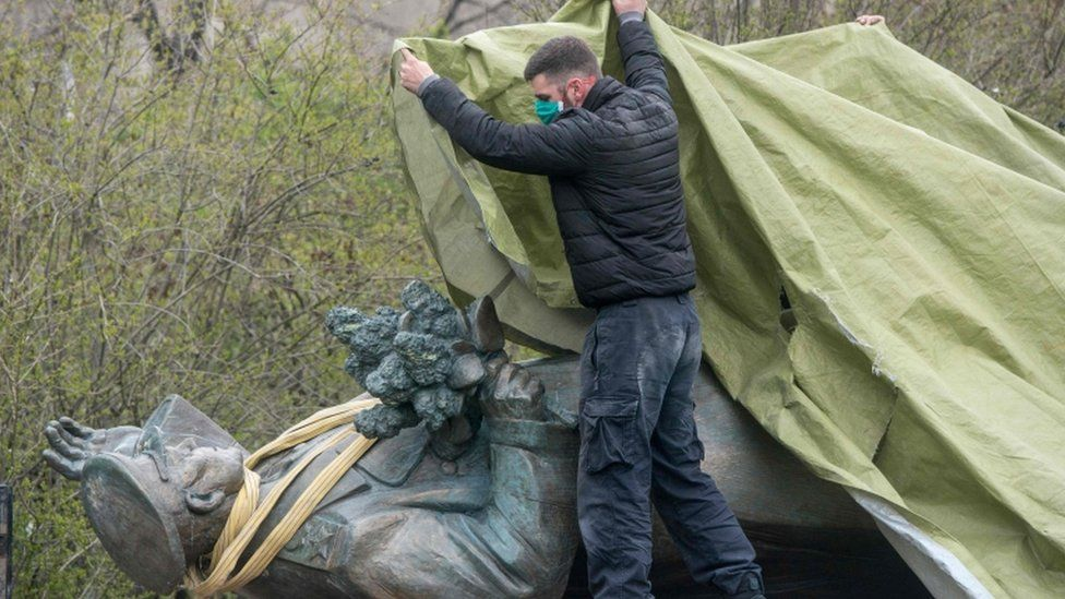 A man covers the statue of Soviet Marshal Ivan Konev laying on a truck during its removal in Prague, 3 Apr 2020