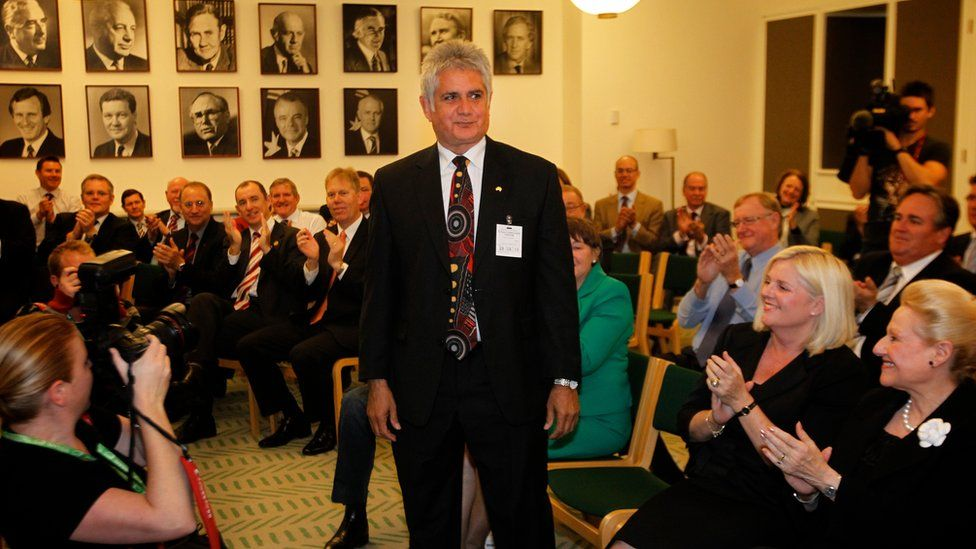 Ken Wyatt stands up in the Liberal party caucus room as other party members applaud