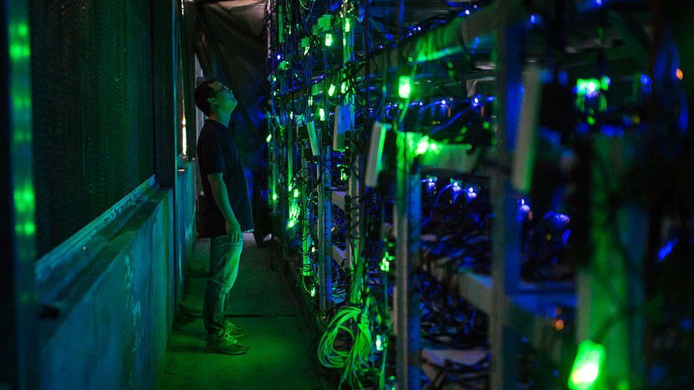 A Chinese bitcoin miner checks mining equipment inside their bitcoin mine in Sichuan province.