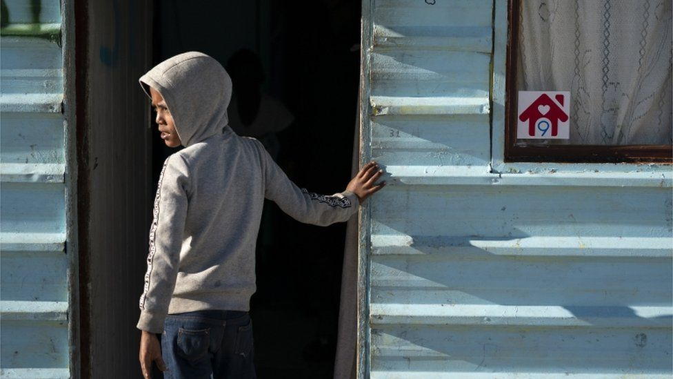 A South African stands next to a home in the Laan settlement in Strandfontein, Cape Town, South Africa.
