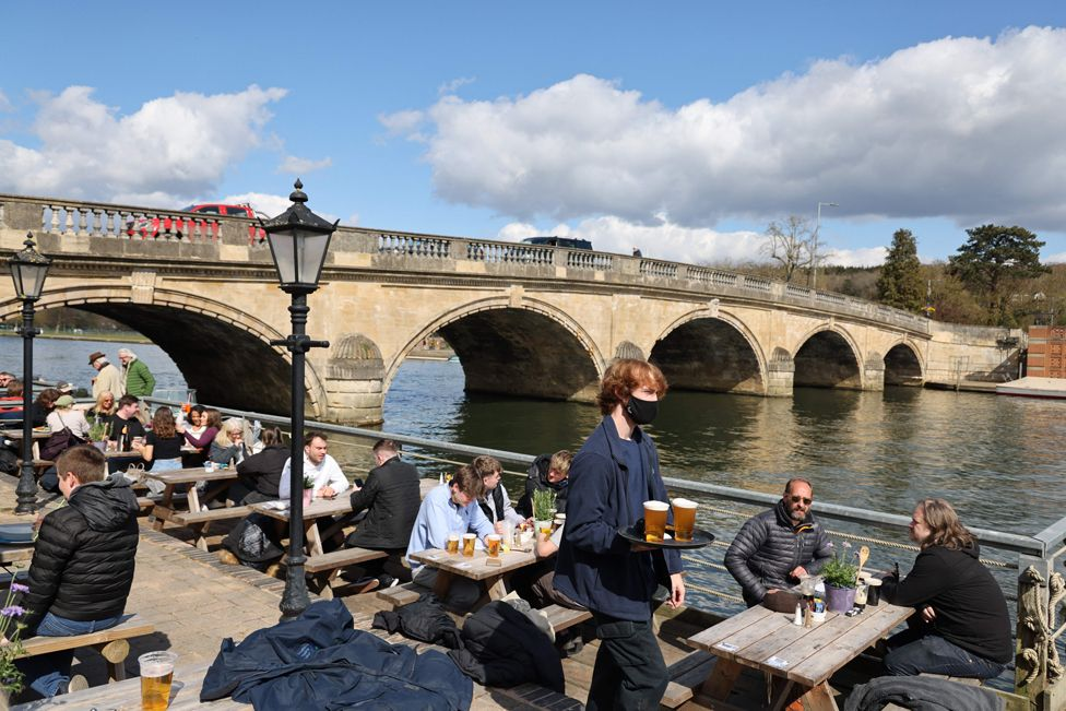 Customers eat and drink on benches next to a bridge
