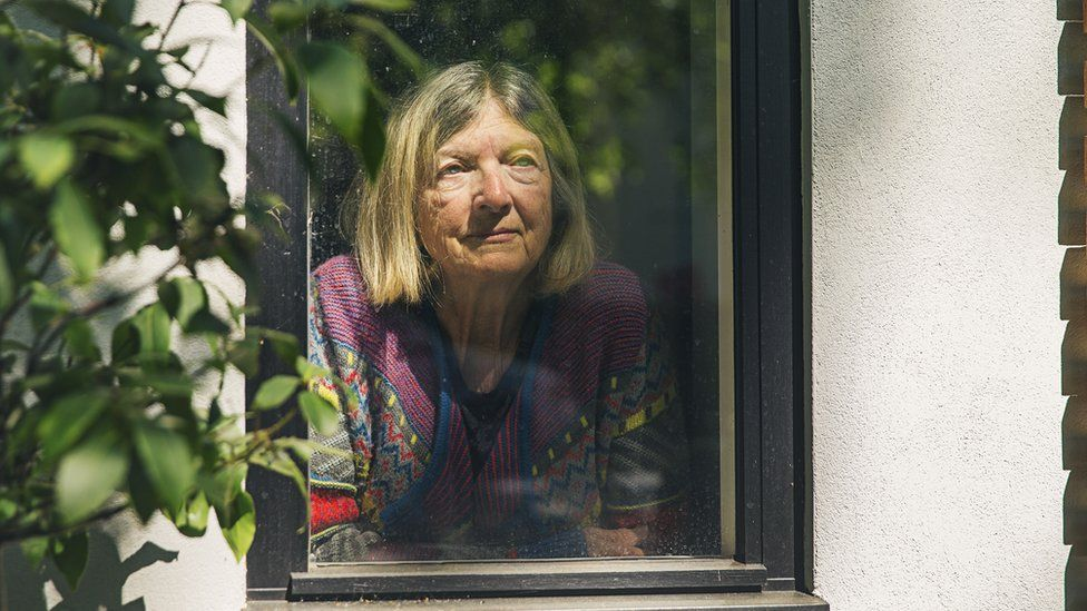 Older woman looking out of her window