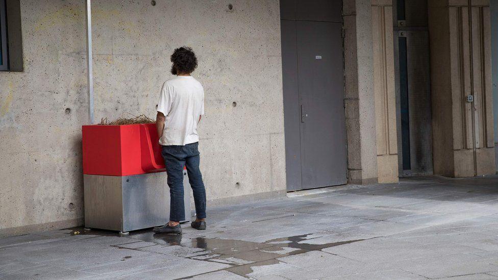 """A man uses a """"uritrottoir"""" public urinal on August 13, 2018"""