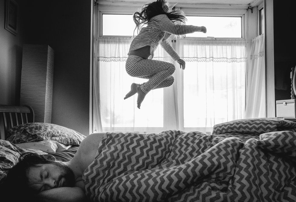 A child jumps on the bed.