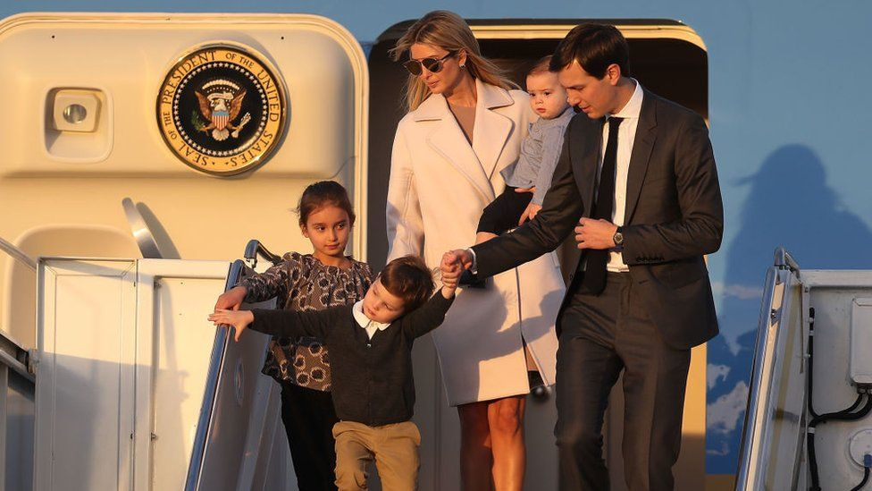 Jared Kushner and his wife Ivanka Trump walk off Air Force One with their children at Palm Beach International airport.