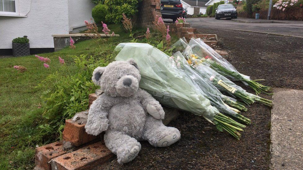 Flowers and a teddy bear at the scene of the crash