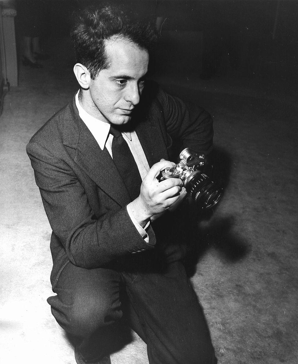Robert Frank holding a pre-war Leica camera, 1954