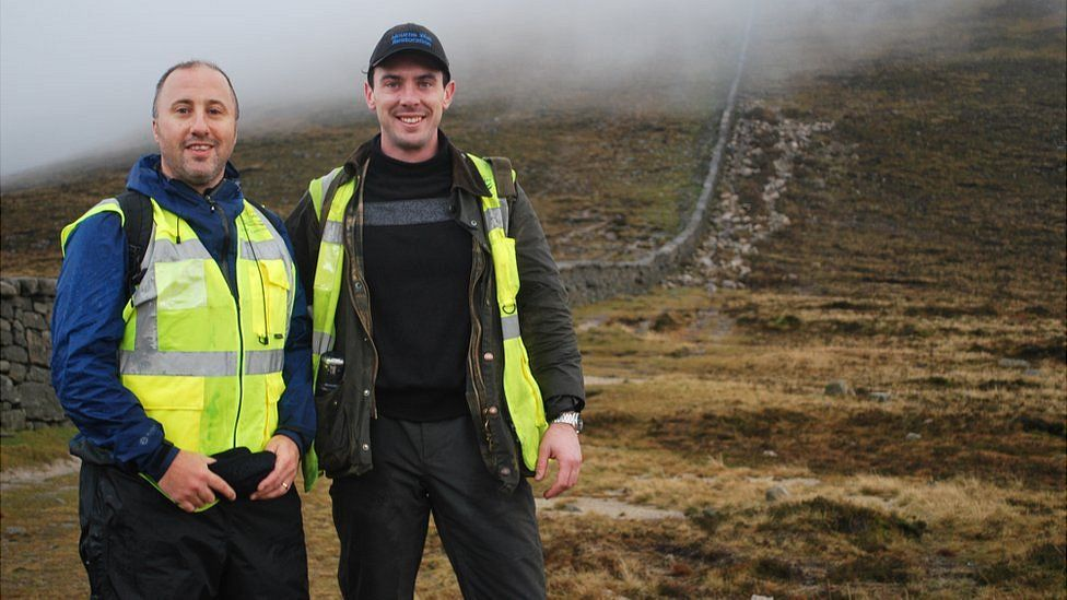 Michal Donnelly and Niall McGovern stand beside the Mourne Wall