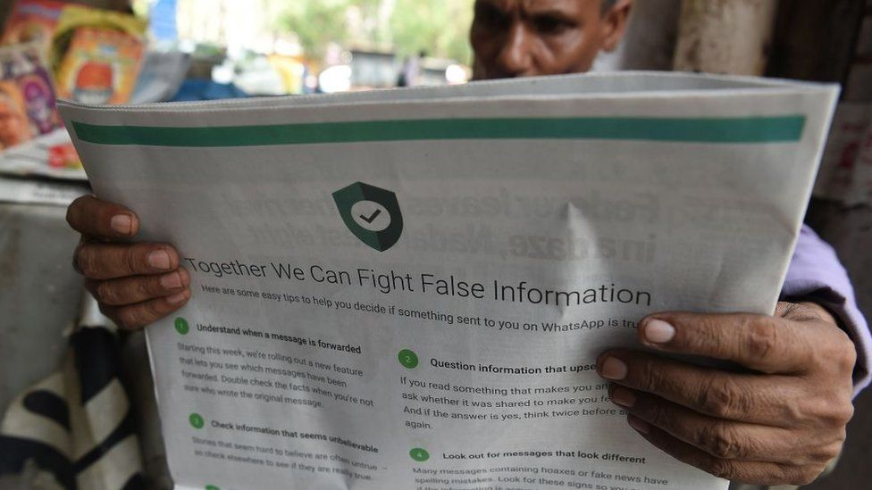 This photo illustration shows an Indian newspaper vendor reading a newspaper with a full back page advertisement from WhatsApp intended to counter fake information, in New Delhi on July 10, 2018
