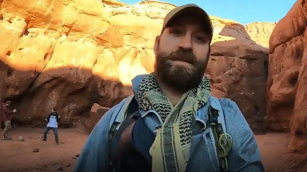 David Surber filming himself inside the canyon near the monolith