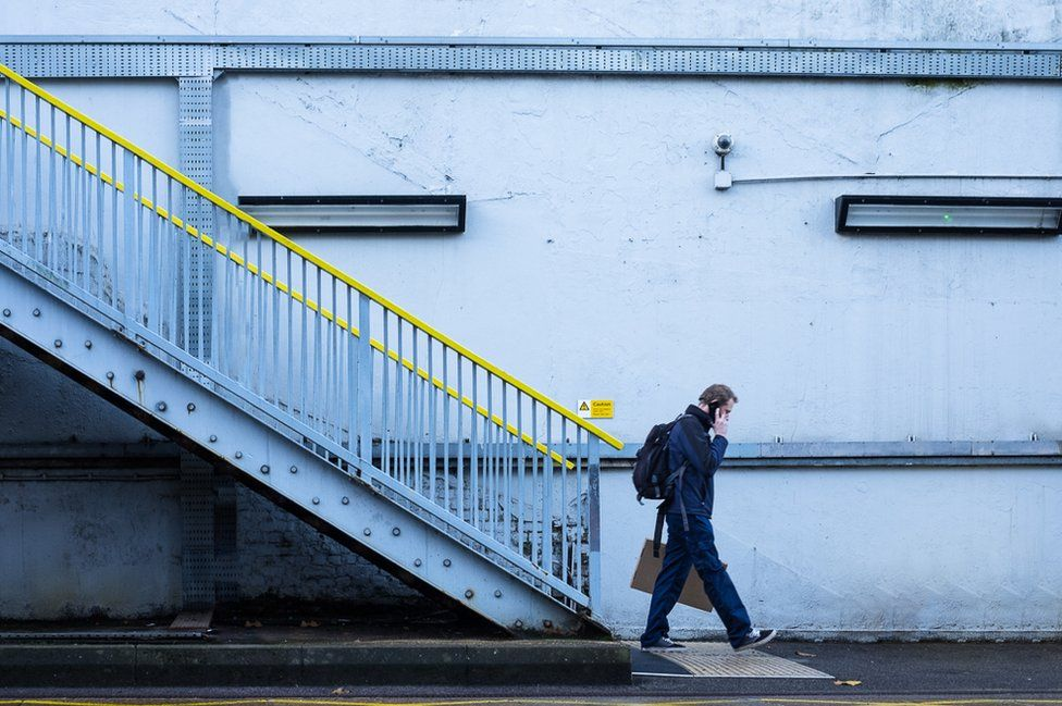 A man walks down a railway platform whilst on the phone