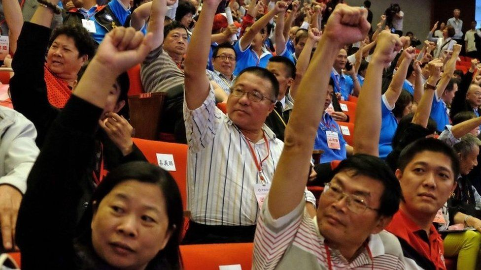 Members of Taiwan's ruling Kuomintang (KMT) raise fists during the party congress in Taipei on October 17, 2015