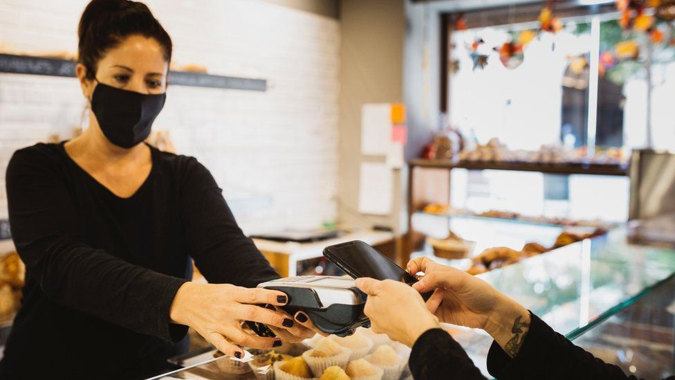Contactless payment in bakery with staff member in a mask