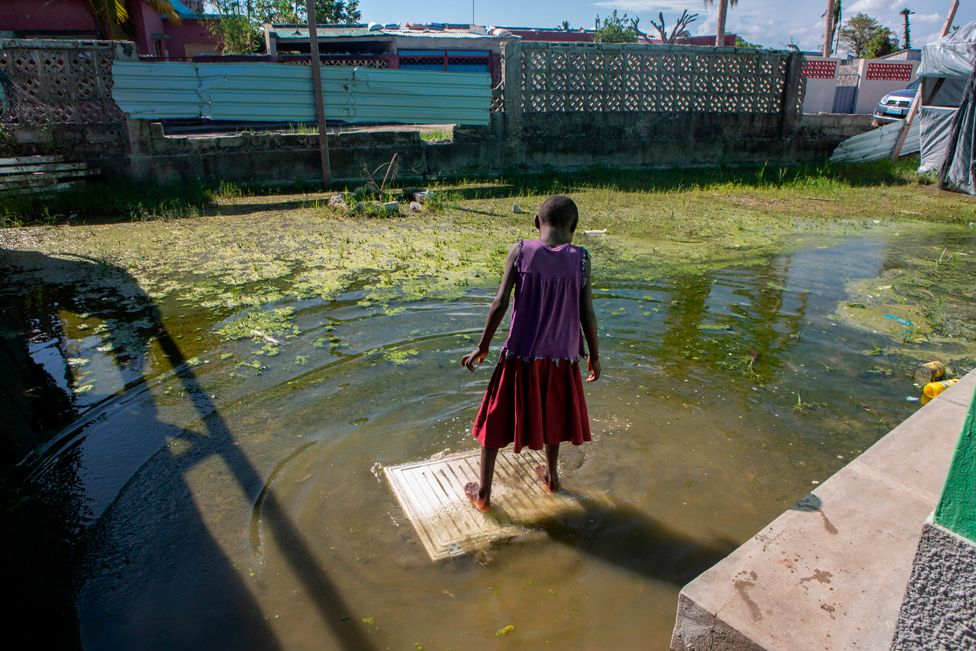 A girl stands on a piece of wood in the flooded courtyard of an elementary school in Beira, Mozambique, on 27 January 2021