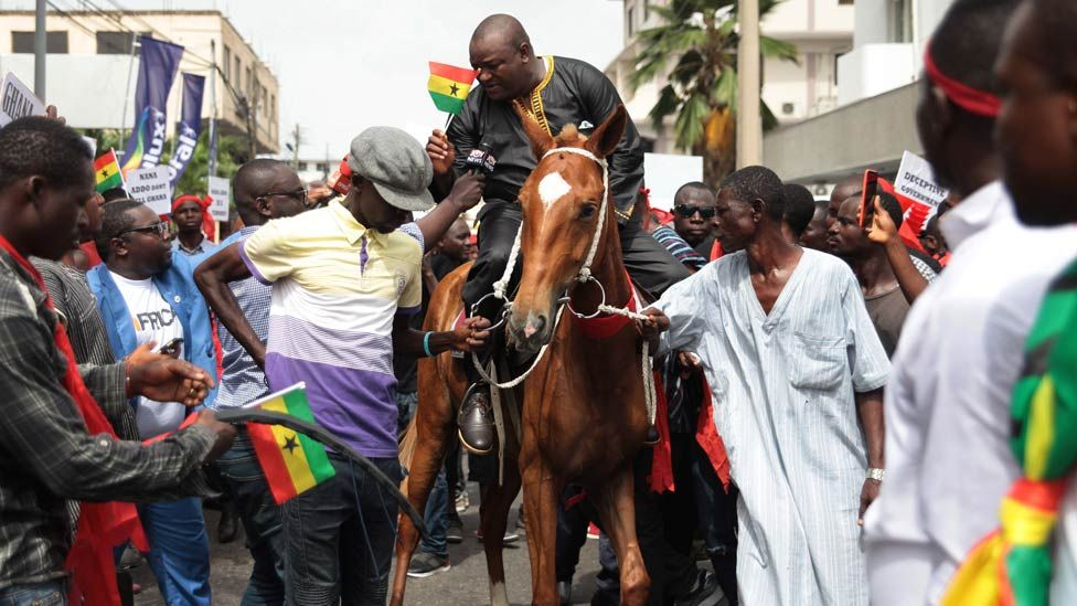 """Hassan Ayariga (C), the founder of the All People""""s Congress (APC) party, rides on horseback during a protest against the expansion of Ghana's defence cooperation with the United States, in the streets of Accra, Ghana 28 March 2018."""