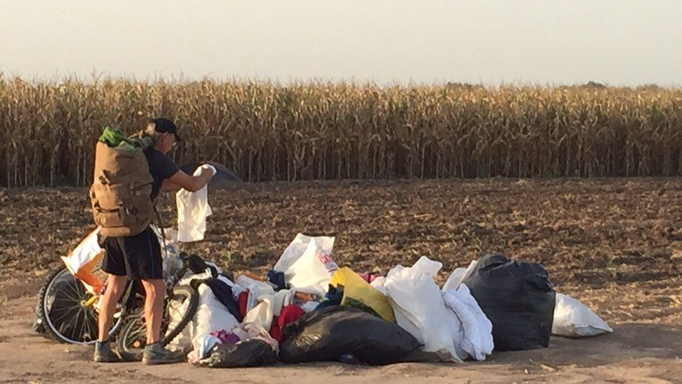 Hungarian man scavenges for clothes abandoned by fleeing refugees