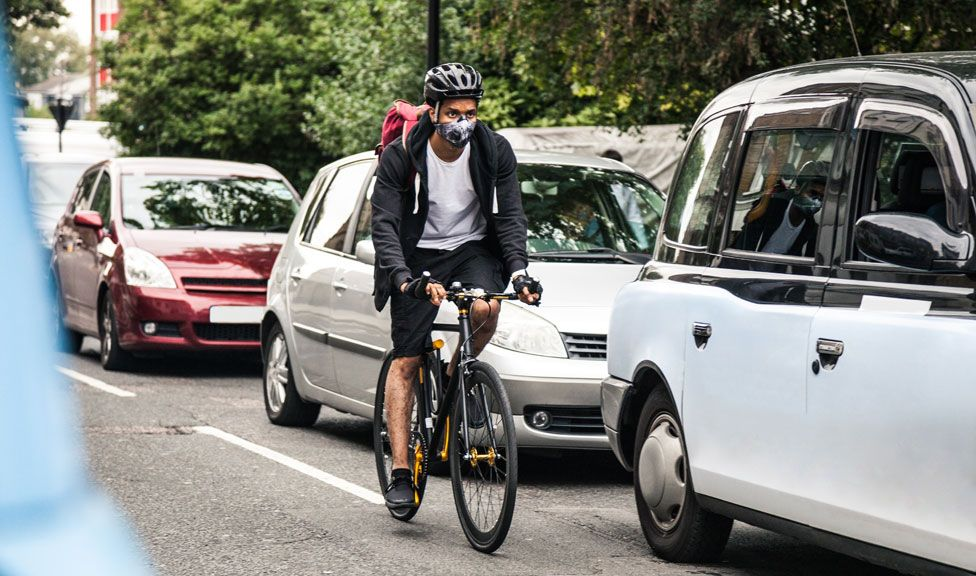 A stock image of a cyclist riding past cars