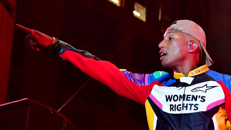 """Pharrell Williams at a concert wearing a T-shirt saying """"Women's Rights"""""""