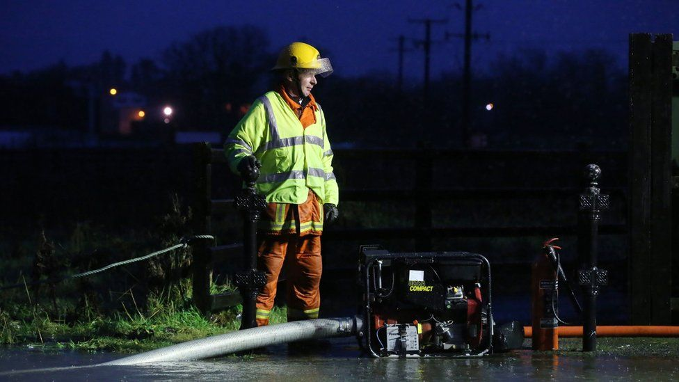 Fire fighter pumps water from a flooded road