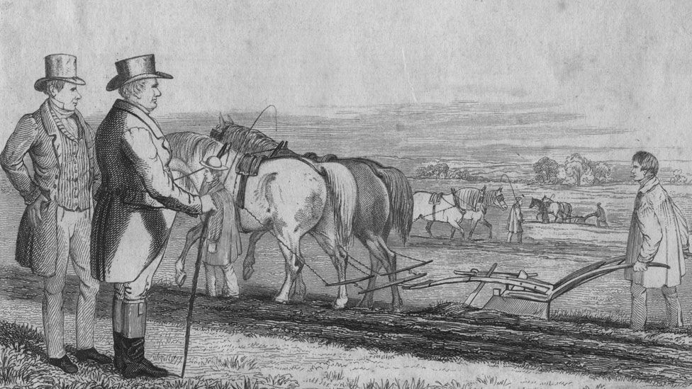 A depiction of two well-dressed men overseeing farm workers ploughing a field, circa 1820