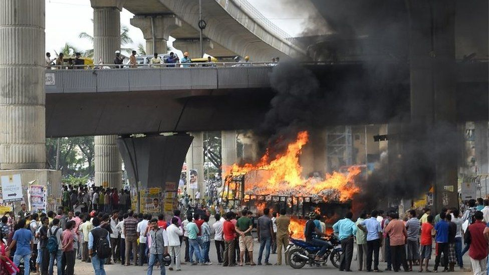 Onlookers watch as a truck from neighbouring state Tamil Nadu burns after it was set alight by agitated pro-Karnataka activists as the Cauvery water dispute erupted following the Supreme Court's order to release water to Tamil Nadu, in Bangalore on September 12, 2016.
