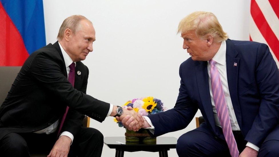 Russia's President Vladimir Putin and former US President Donald Trump shake hands