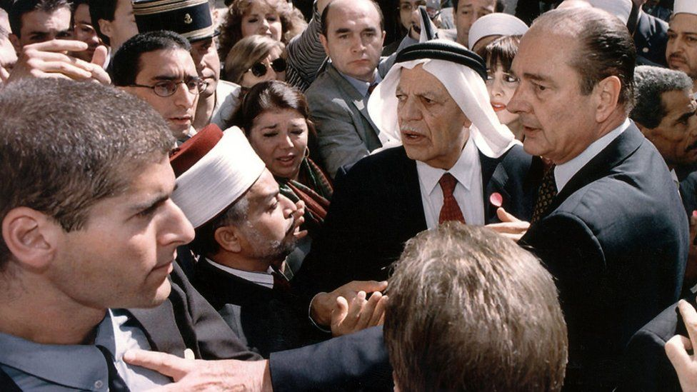French President Jacques Chirac puts his hand on an Israeli security guard in Jerusalem on 22 October 1996