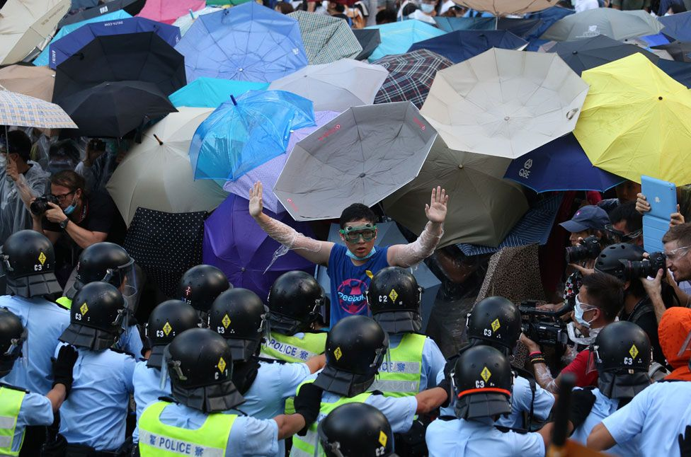 A man wearing goggles and cling film raises his hands to gathered police, as behind him, dozens of umbrellas are unfurled