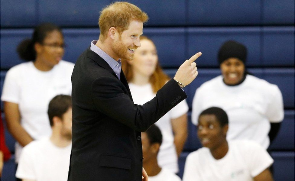 Prince Harry beams and points a finger at the Coach Core awards at Loughborough University