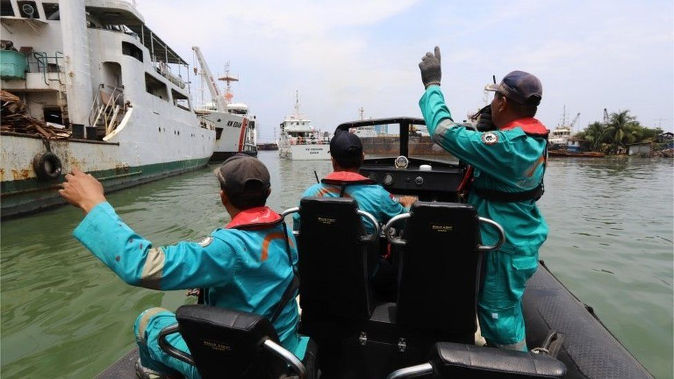 Search and rescue officials wave from a boat