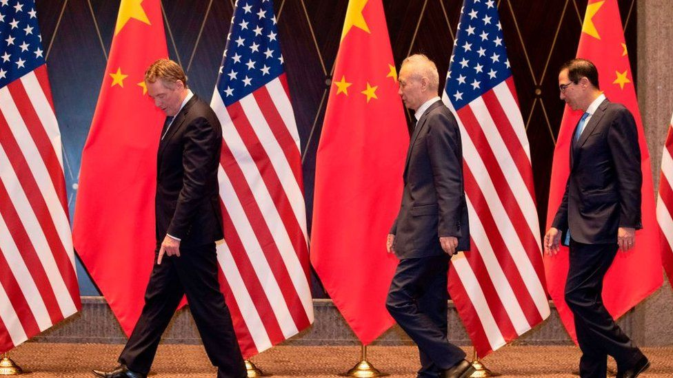 """US Trade Representative Robert Lighthizer (L) points at markers on the floor as he leads Chinese Vice Premier Liu (C) and US Treasury Secretary Steven Mnuchin (R) to their positions for a """"family photo"""" at the Xijiao Conference Centre in Shanghai on July 31, 2019"""
