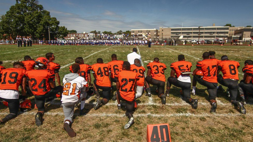 The Tigers kneel at the start of Saturday's game