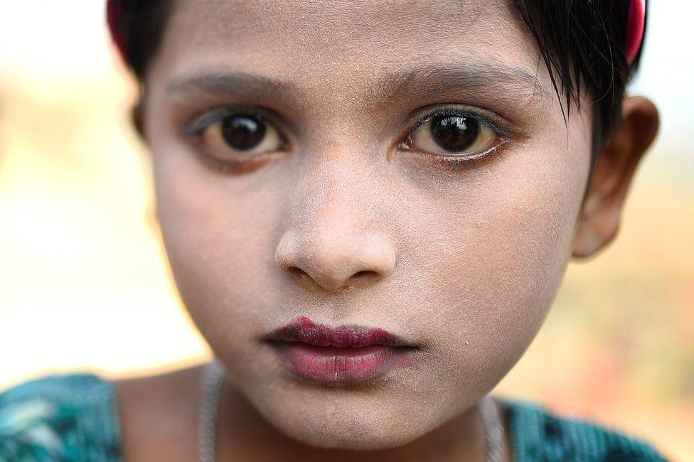 Rohingya refugee Sufaida, aged 7, poses for a photograph as she wears thanaka paste at Kutupalong camp in Cox's Bazaar, Bangladesh