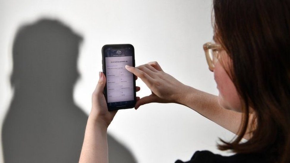 A staged photo of a person using the Australian government's coronavirus tracking app on a phone