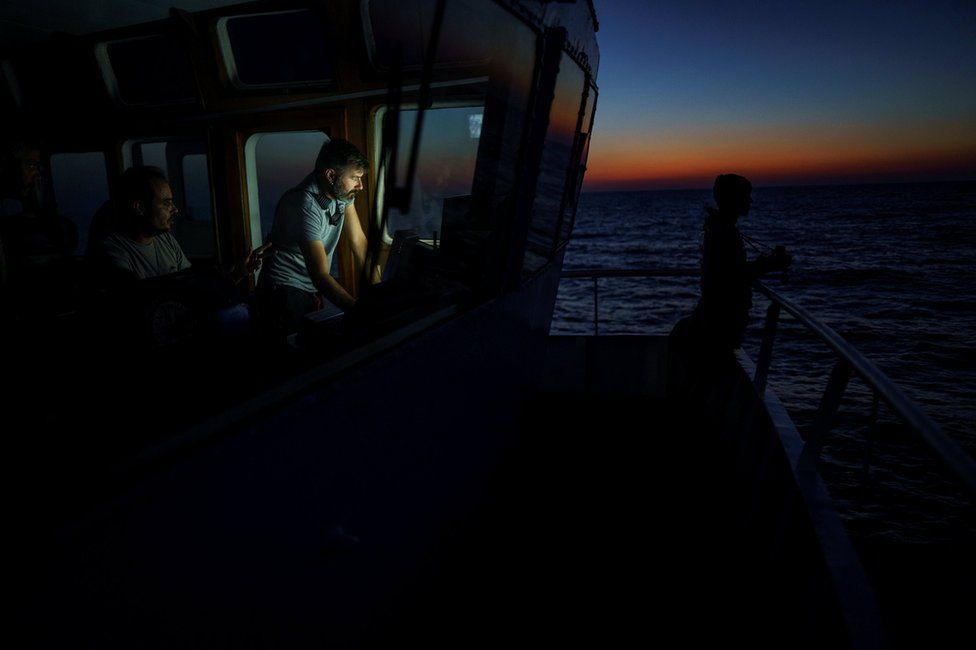 Head mission of NGO Proactiva Open Arms Riccardo Gatti tracks the position of a rubber boat in central Mediterranean Sea