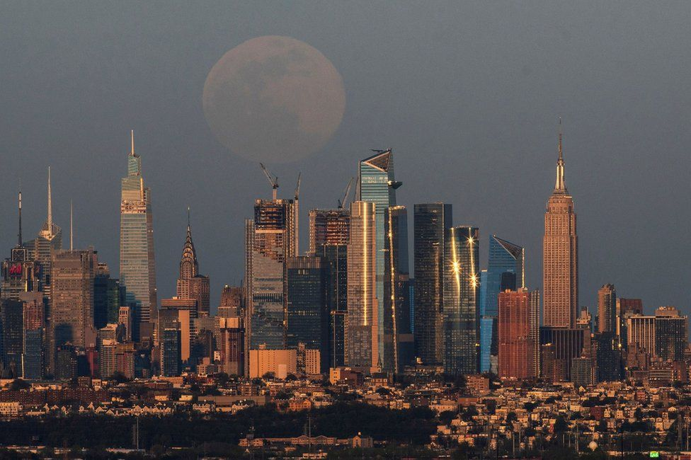 The skyline of New York and the Empire State Building with the pink supermoon in the sky
