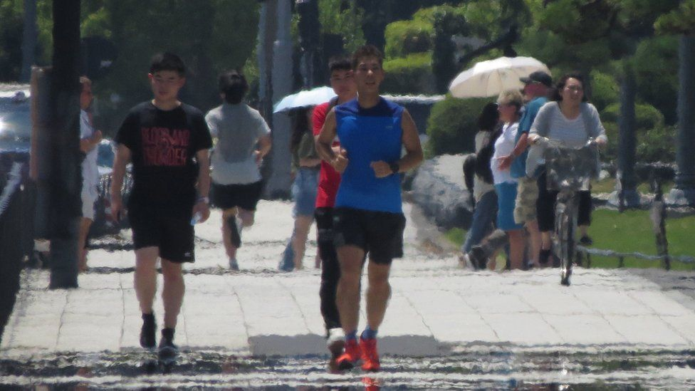 The effects of heat haze are seen as pedestrians walk along a street during a heatwave in Tokyo on August 2, 2018