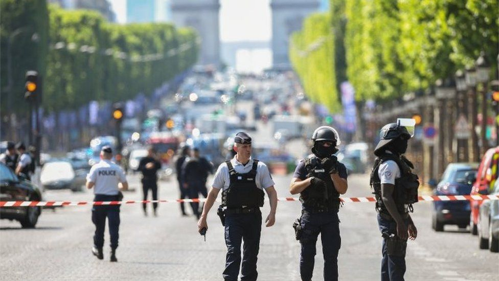 Police officers and anti-riot police officers patrol the Avenue des Champs-Élysées on 19 June 2017