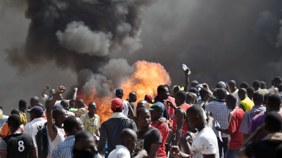 People stand in front of smoke rising from the Burkina Faso's Parliament, where demonstrators set cars on fire parked in a courtyard of the Parliament, on October 30, 2014 in Ouagadougou, as they protest